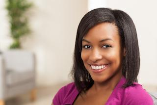 young woman sitting & smiling I gum disease treatment at azalea dental