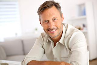 middle-aged man facing forward with bright smile I porcelain veneers at azalea dental