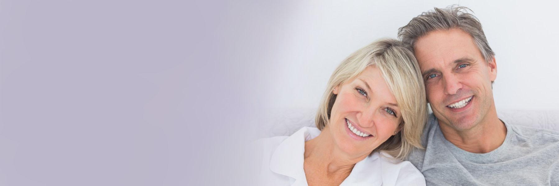 Middle-aged couple smiling & hugging l Dental implants Summerville SC