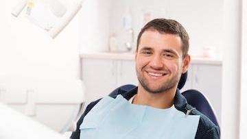 Man smiling sitting in dental exam chair l Dental exam Summerville SC